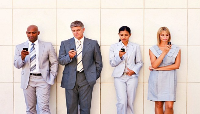 Group of business associates in a line text messaging on their cellphone